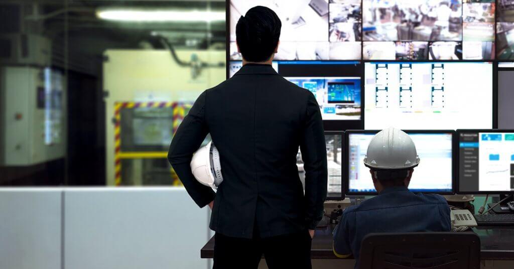 mannen kijken naar schermen in fabriek